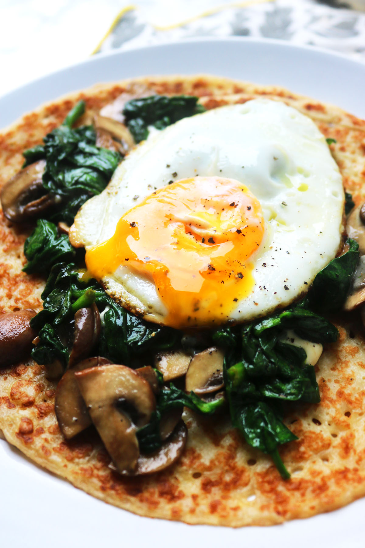 Thin crepes topped with spinach and mushroom, crumbled stilton and a gooey fried egg! The perfect breakfast, brunch or dinner!