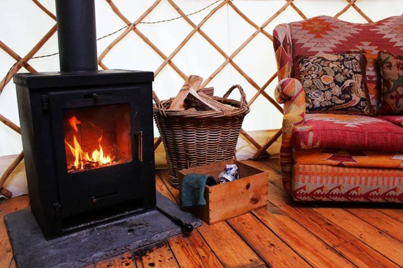Home comforts like a sofa and wood burner are essential in a yurt when glamping off grid