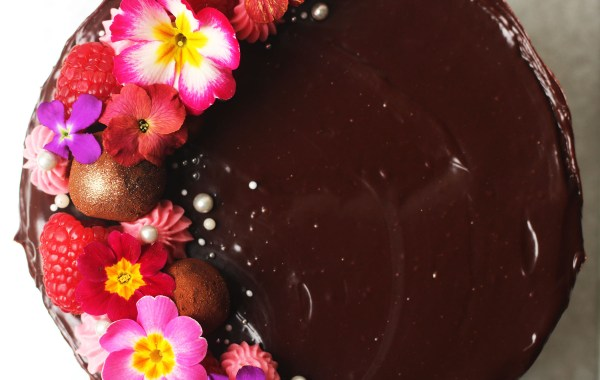 Cake covered in chocolate ganache and topped with truffles, rasbperries and edible flowers