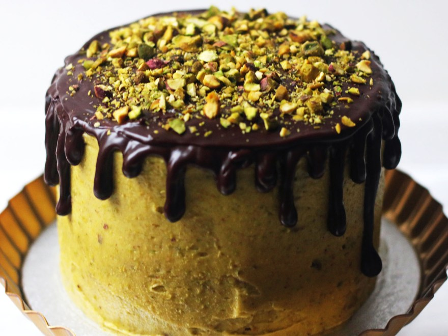 Chocolate and Pistachio Cake on a gold cake stand with chocolate ganache drips and chopped pistachios