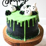 Halloween layer cake: Coconut and Lime Slime Cake. Decorated with black buttercream and green white chocolate ganache drip and coconut meringue ghosts.