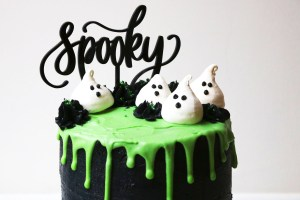 Coconut sponge cake decorated with black buttercream and green white chocolate ganache drip, coconut meringue ghosts and a spooky cake topper