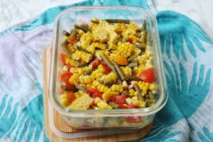 Sweetcorn, green bean and tomato salad in a glass and bamboo storage container