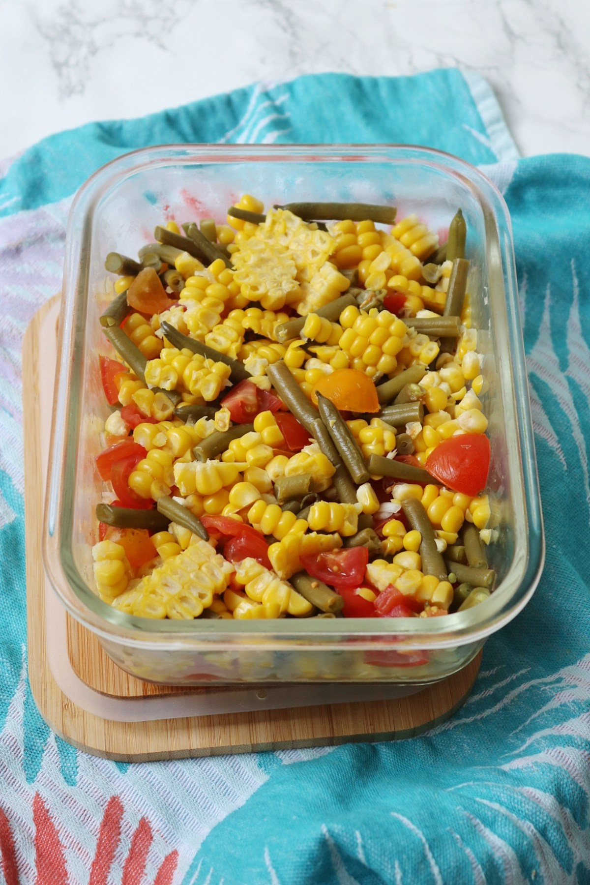 Sweetcorn, green bean and tomato salad in a glass container with bamboo lid