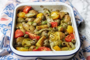 A roasting tin of fennel, potatoes, tomatoes and olives