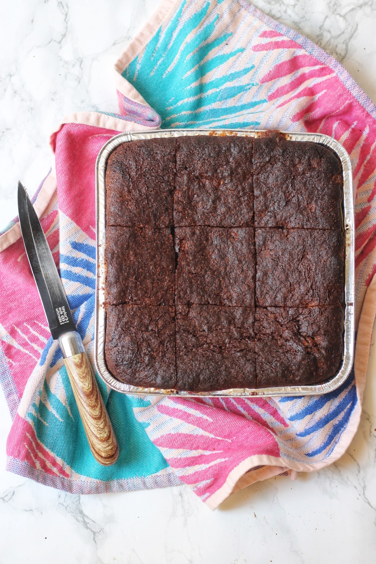 A tray of vegan brownies with a knife