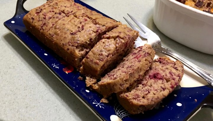 Cranberry and Toasted Pecans Holiday Bread on a Christmas serving platter. Sliced with a serving fork.