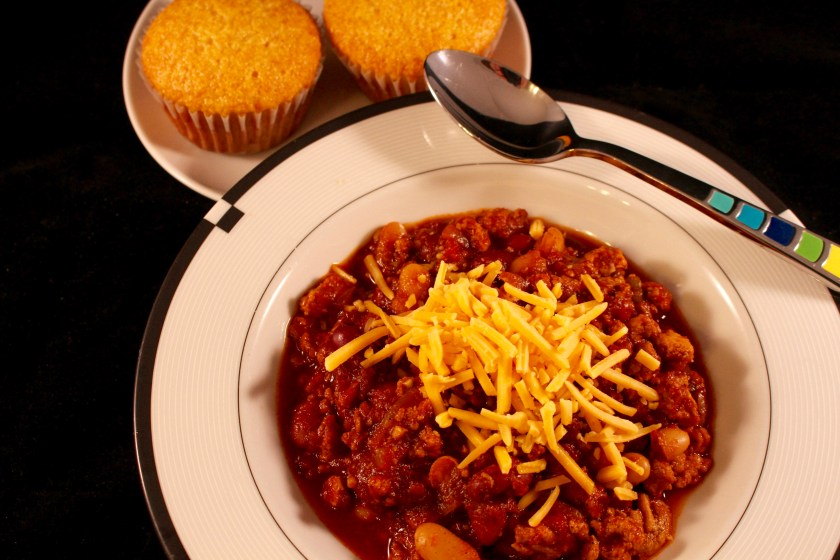 Bowl of chili with cheddar cheese on top in a white bowl with a spoon and cornbread muffins along the side