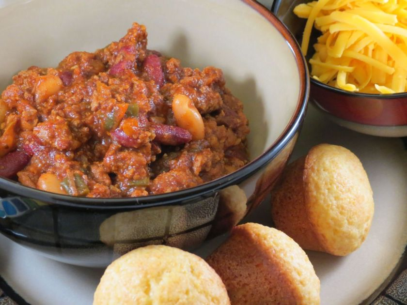 Chili in a bowl with mini cornbread muffins around the bowl