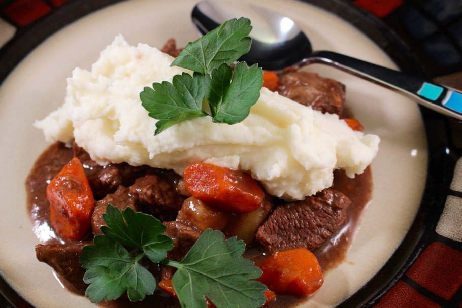 Beef Stew with Parsnips on a white plate topped with mashed potatoes with a spoon