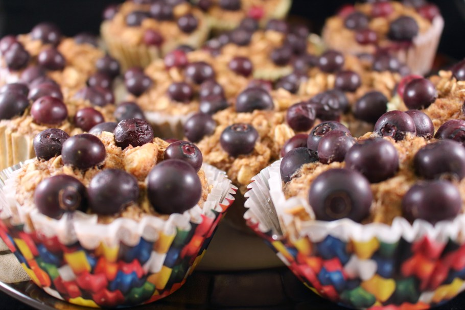 A side view of Blueberry Banana Oatmeal Muffins with a bubblegum liner over the white baking liner