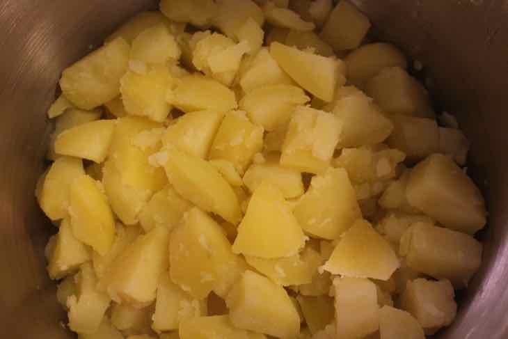 Cooked cubed potatoes in a pot