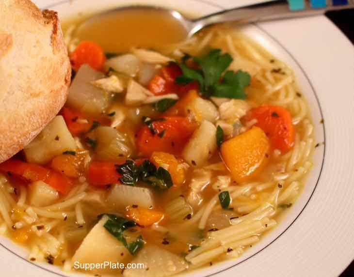 Chicken Noodle Soup with crusty french bread in a white bowl