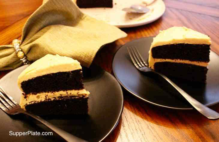 Tow slices of chocolate cake on black plates