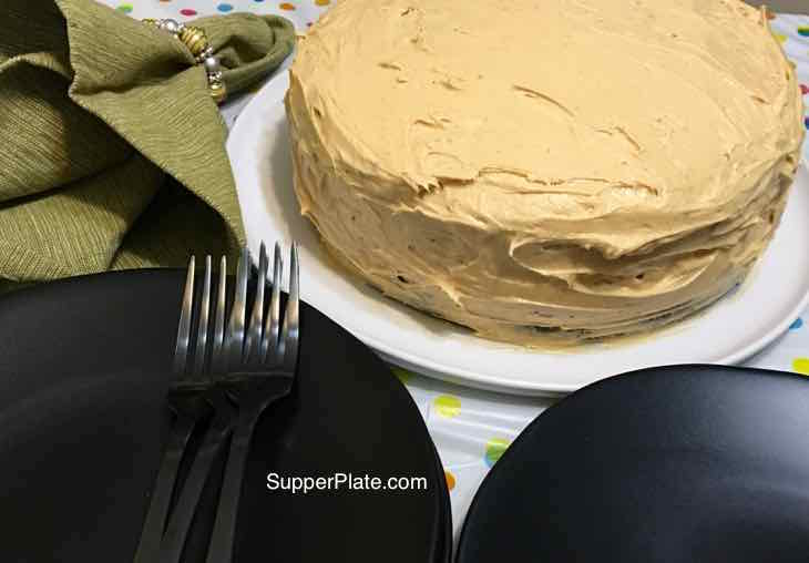 Chocolate Cake after adding Peanut Butter Frosting on a white plate