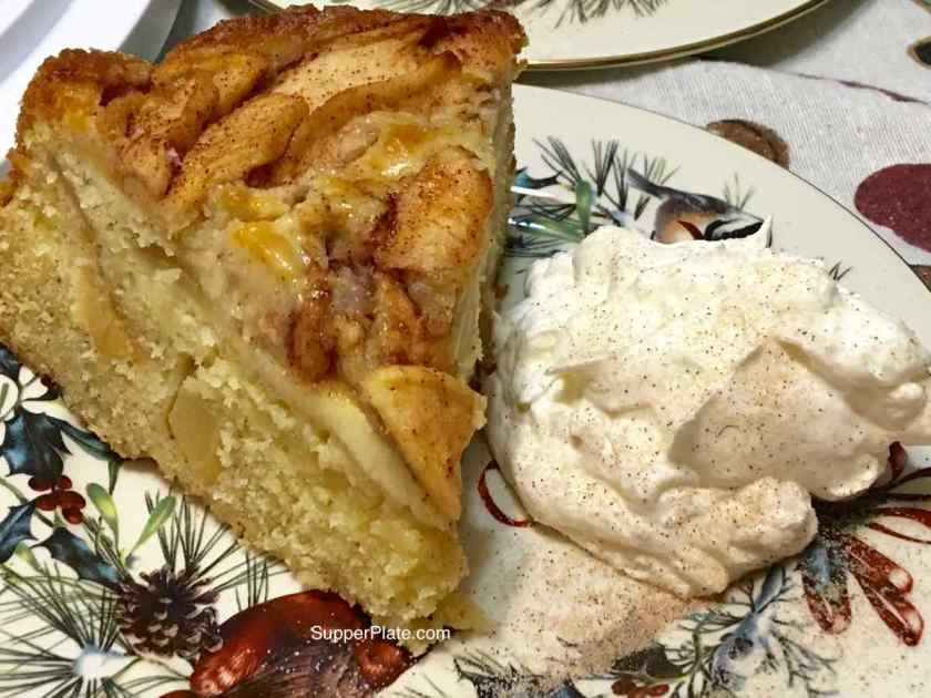 Apple Cinnamon Cake plated with a side of homemade whipped cream topped with cinnamon sugar