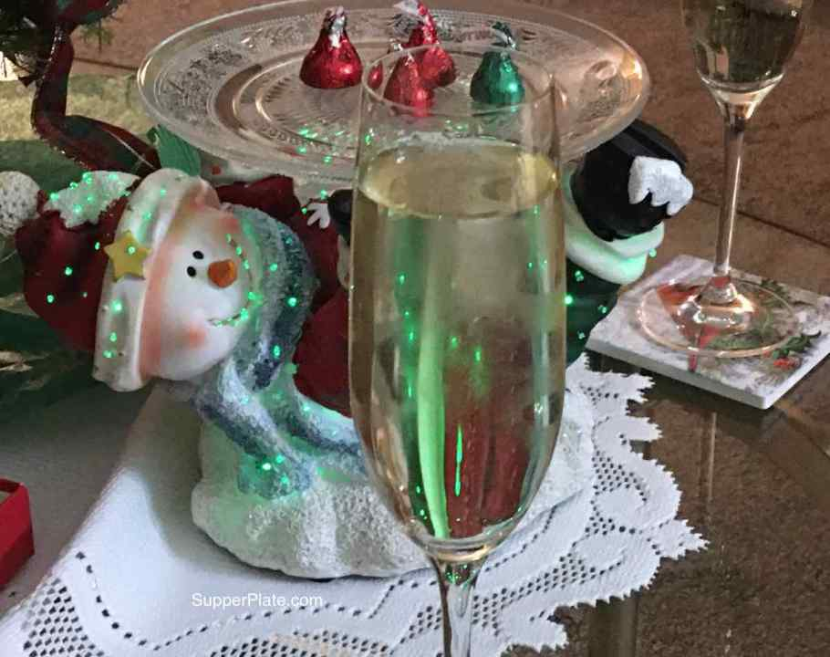 A snowman Christmas candy dish with Hershey kisses in red and green wrappers. A champagne glass in front of the light up snowman.