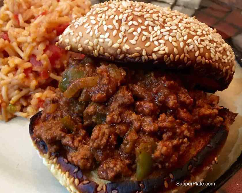 Homemade sloppy joes served on a toasted seeded roll with a side of Spanish rice