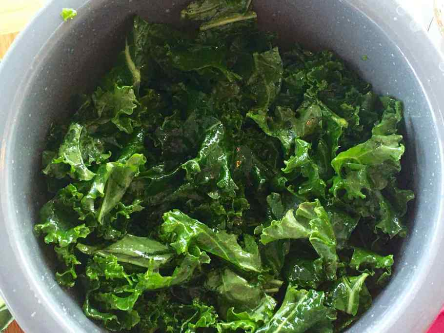 Kale in a bowl mixed with the dressing