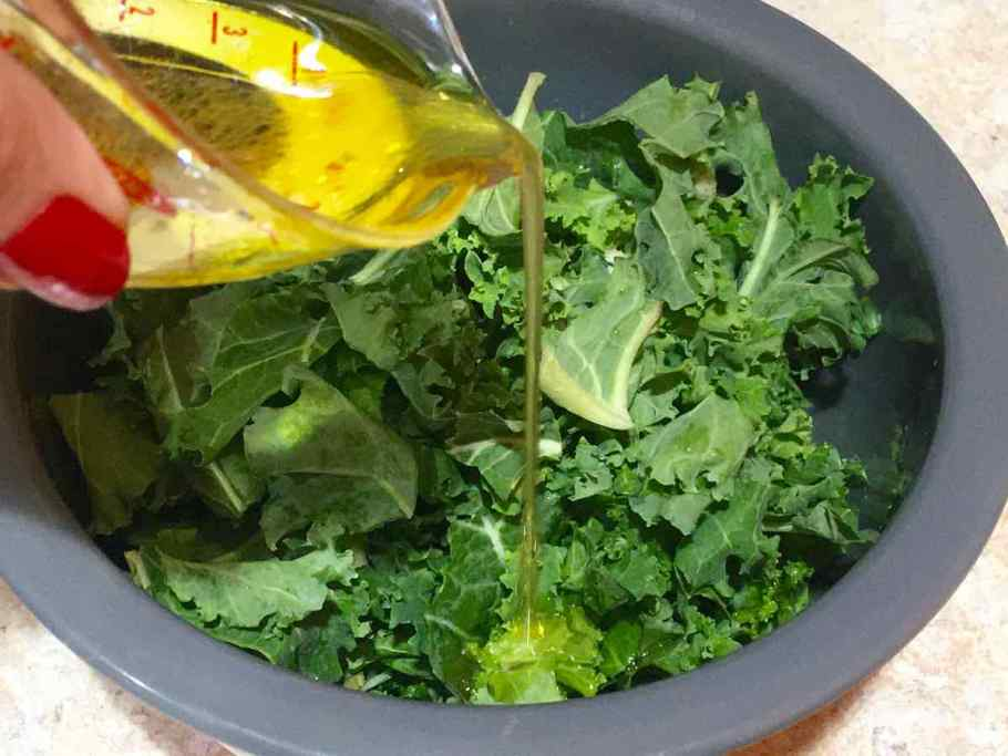 Pour olive oil and vinegar over kale in a bowl