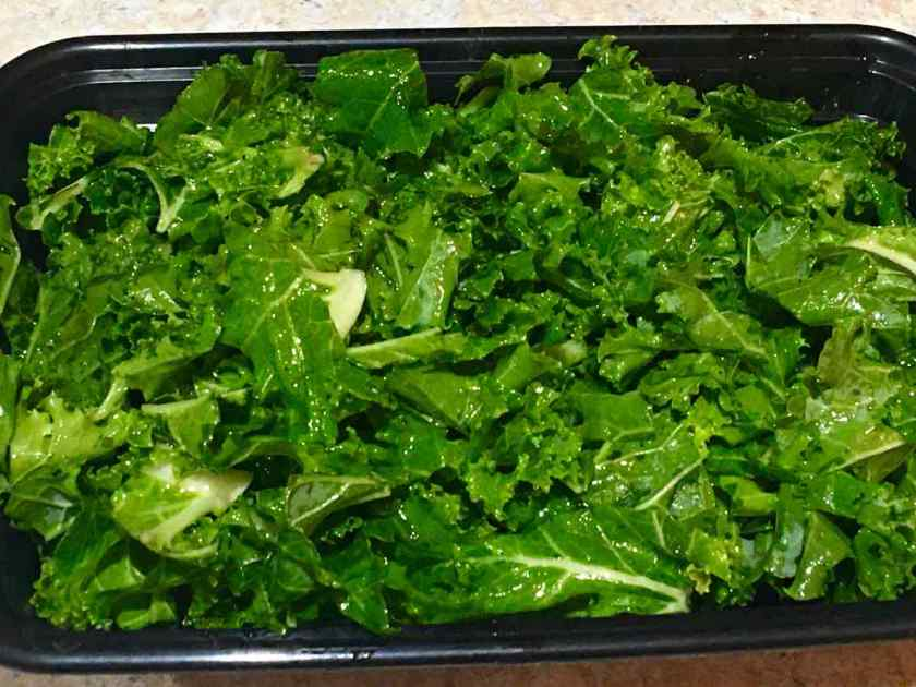 Kale with oil and vinegar in a container