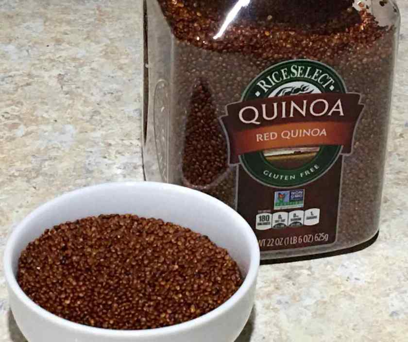 Red Quinoa in a container and in a small white bowl uncooked