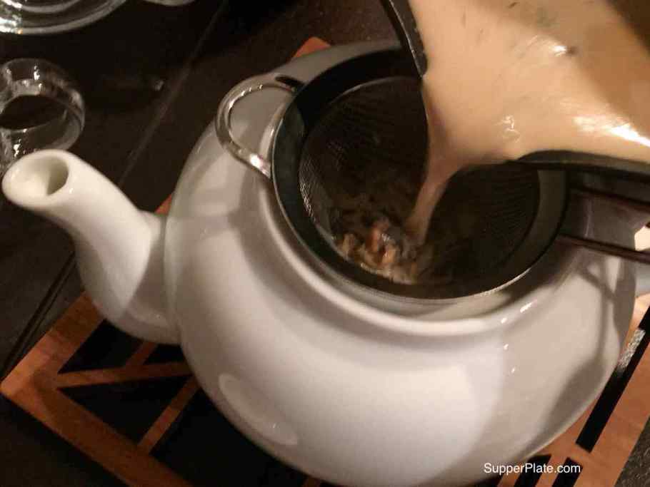 Pouring the tea from the pot into a strainer over a white tea pot