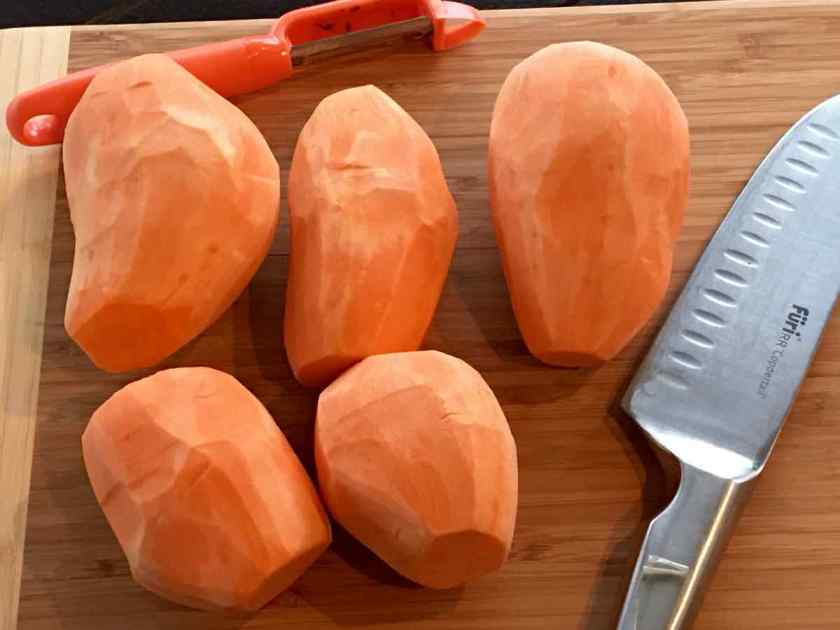 Sweet potatoes peeled on a wood cutting board with a vegetable peeler and knife
