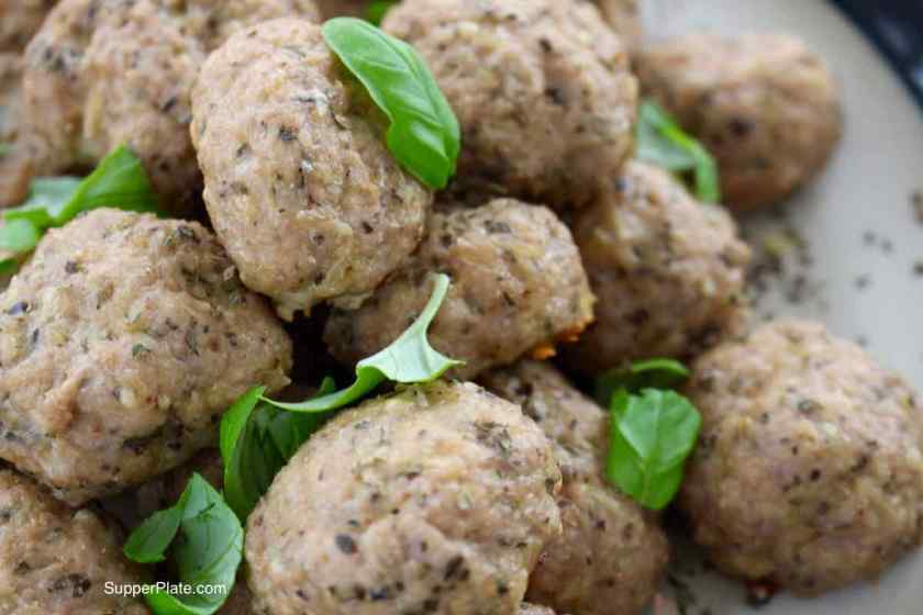 Baked Mini Turkey Meatballs Closeup picture on a plate topped with fresh basil