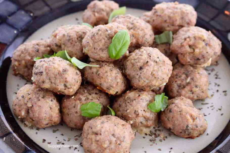 Side View of Baked Mini Turkey Meatballs Closeup picture on a plate topped with fresh basil