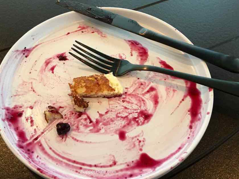 White Plate with remains of blueberry sauce with black fork and knife