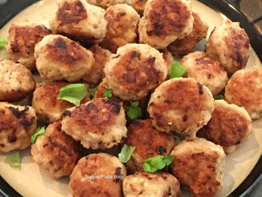 Top view of Mini Meatballs that are browned on a plate topped with fresh and dried basil on a plate