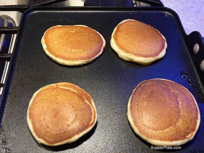 Four browned pancakes on a griddle