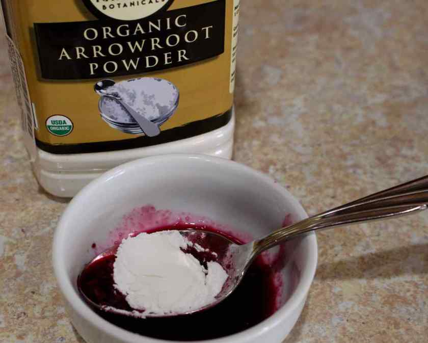 Adding arrowroot to the small bowl with blueberry sauce. Arrowroot powder in a container is behind the small bowl.