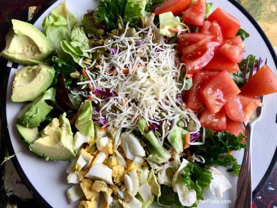 Top view of a kale salad with tomatoes avocados and hardboiled eggs