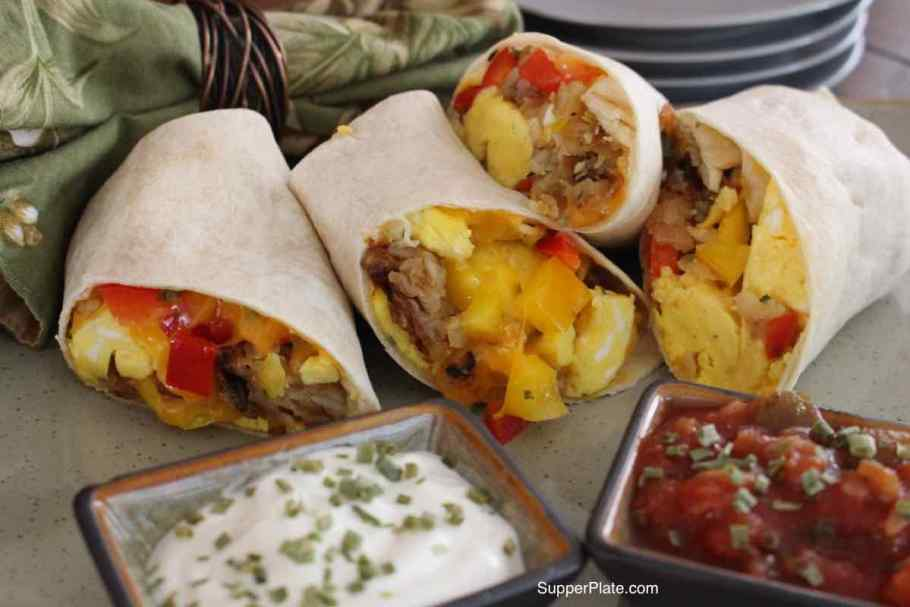 Four Meal Prep Breakfast Burritos on a platter with sour cream and salsa