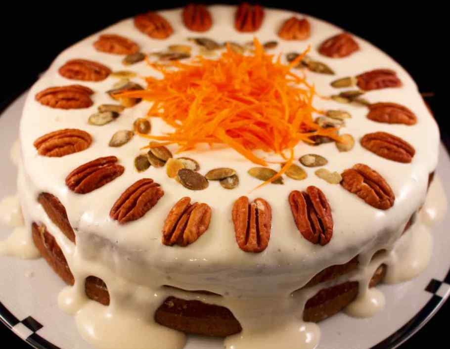 Finished cake with icing, whole pecans, raw pumpkin seeds and shredded carrots