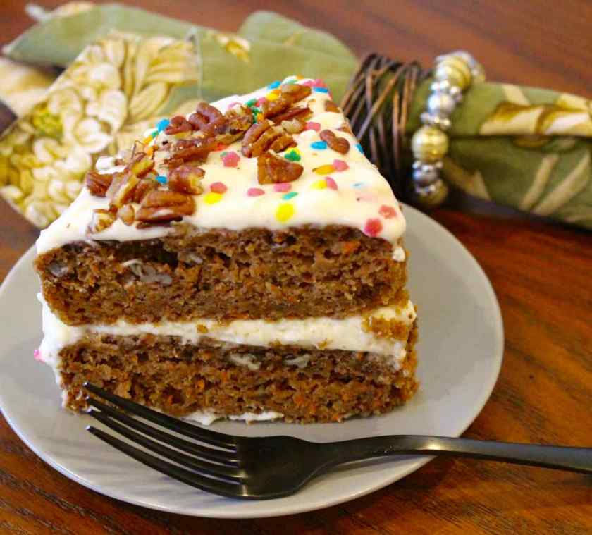 Slice of Carrot Applesauce Cake on a green plate with a black fork and green napkin