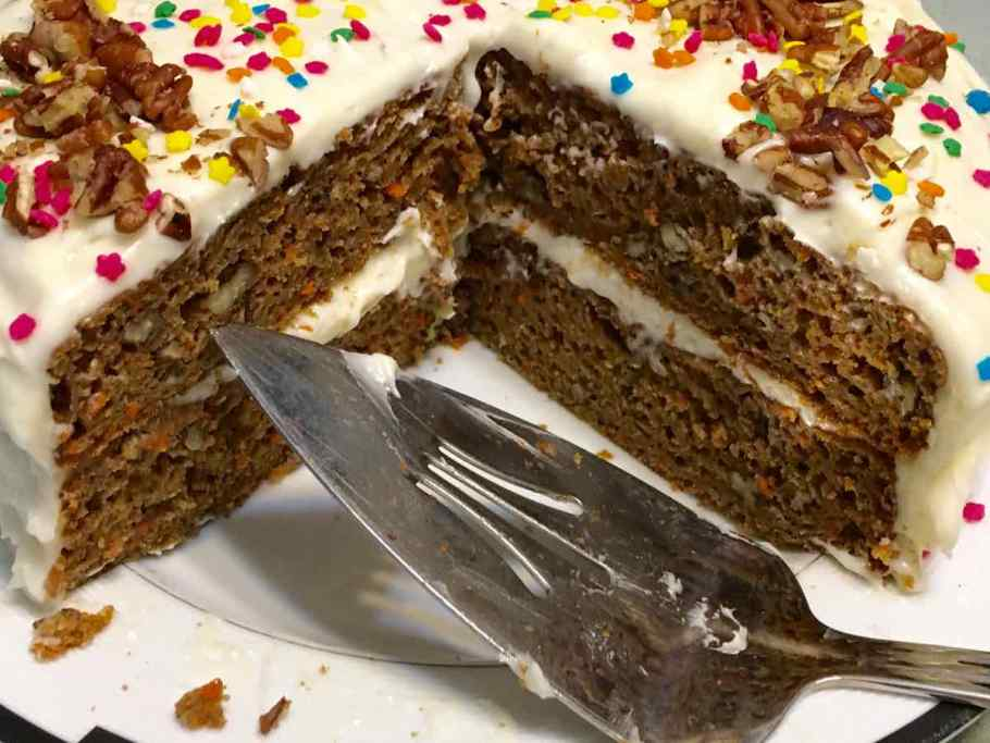 Carrot Applesauce Cake on a white plate with a couple slices gone with a cake serving spatula