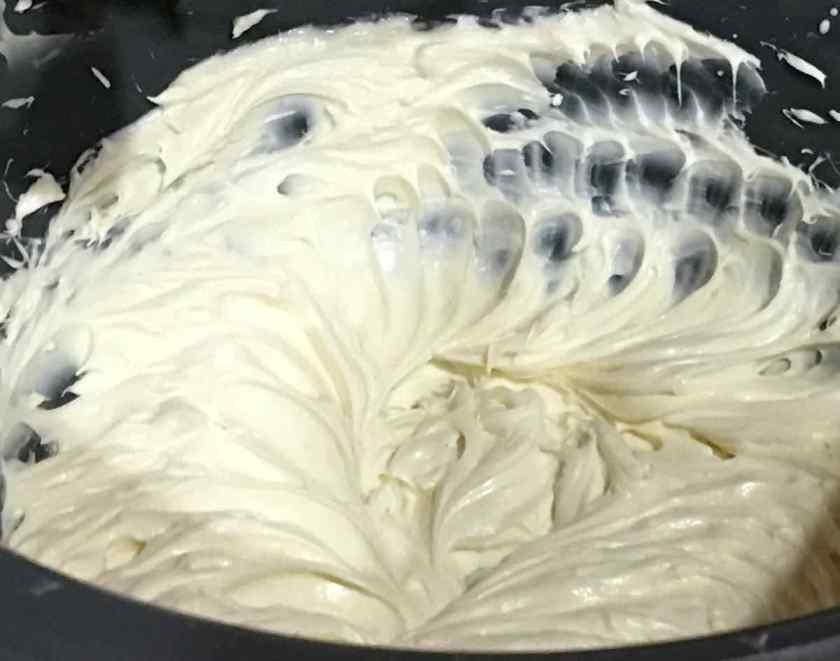 Fluffy cream cheese frosting in a bowl