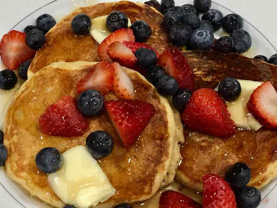 A stack of pancakes with butter and berries
