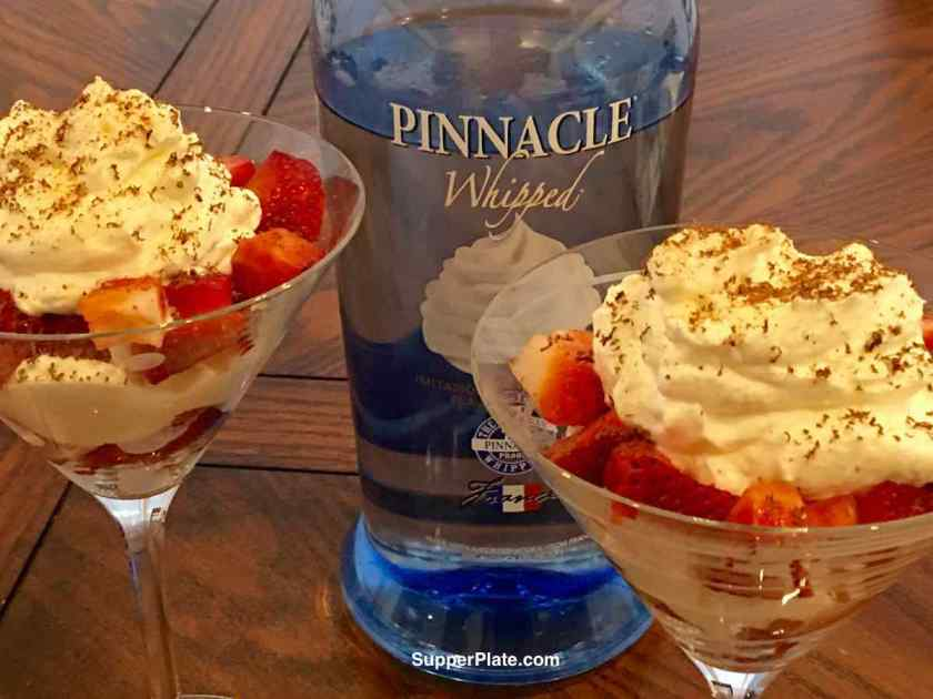 Strawberries Whipped Cream with Pinnacle Whipped Vodka bottle in the background