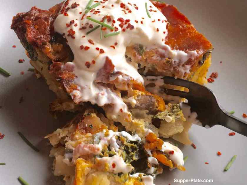 Breakfast Casserole with Bacon on a plate topped with sour cream with a fork cutting into it