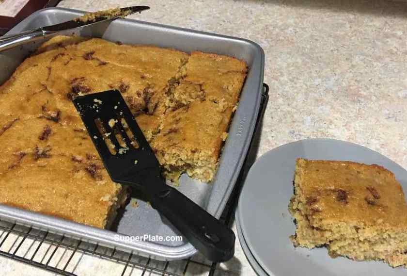 Rhubarb Coffee Cake served on a green plate next to the coffee cake pan