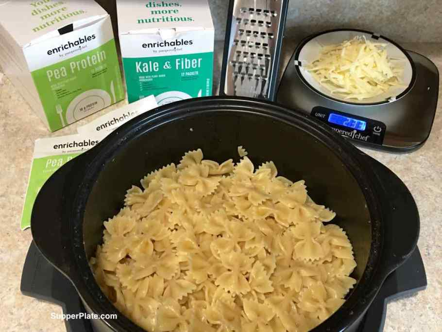 Cooked pasta in a dutch oven with cheese and enrichables in the background