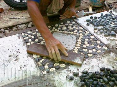 Ketuk-ketuk dengan papan kayu agar batu masuk ke dalam adukan semen.