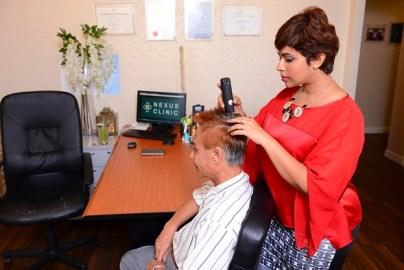 Dr. Jasmine Ruth dari Nexus Medispa melakukan pemeriksaan kulit kepala menggunakan kamera rambut.