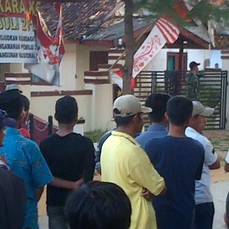 Meski sudah dijaga anggota TNI, beberapa massa masih terlihat bergerombol di depan Polsek Arjasa, beberapa saat setelah kerusuhan dapat diredam. (FOTO : surabayaupdate.com)