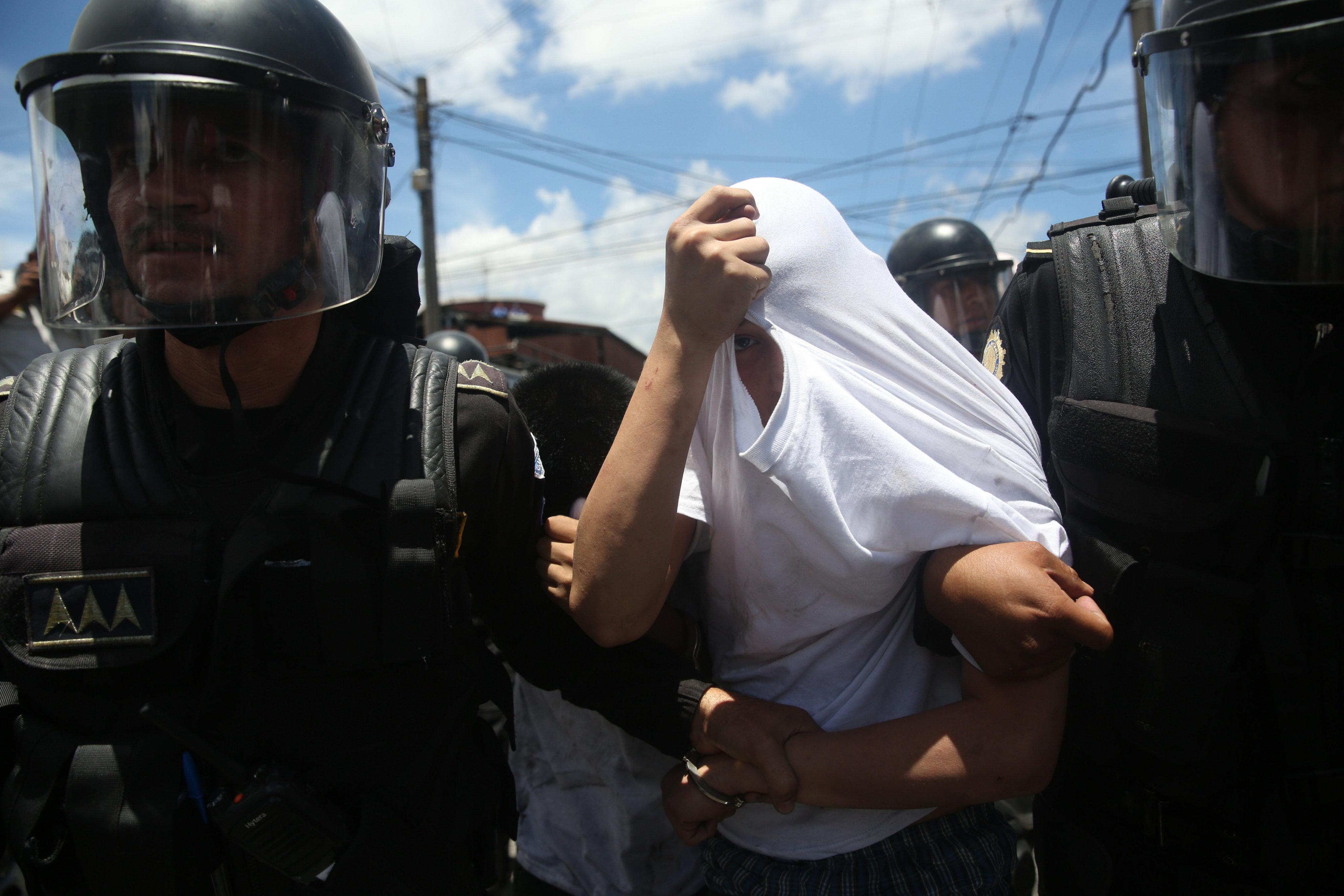 """GU1001. CIUDAD DE GUATEMALA (GUATEMALA), 24/07/2017.- Agentes de policías detienen a un recluso que intentó huir de un centro correccional de menores, hoy, lunes, 24 de julio de 2017. Al menos 12 presos resultaron heridos este luns en un nuevo motín en el correccional """"Las Gaviotas"""", informaron fuentes oficiales. El ministro de Gobernación (Interior), Francisco Rivas, explicó en rueda de prensa que el motín se inició por una riña entre dos grupos de detenidos conocidos como """"los paisas"""" y la """"Mara Salvatrucha"""". EFE/Esteban Biba"""