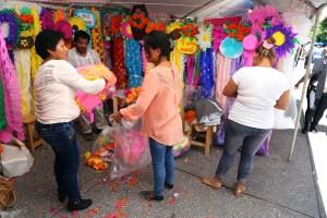 Una joven compra una cortina de papel en los puestos que se instalaran en el Centro de Chilpancingo, para el festejo del 10 de Mayo, Día de las Madres. Foto: Jesús Eduardo Guerrero